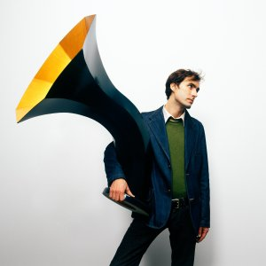 Andrew Bird, holding a Victrola.